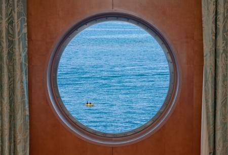 windows: Two woman in a kayak on the open ocean as seen through the porthole of a cruise ship