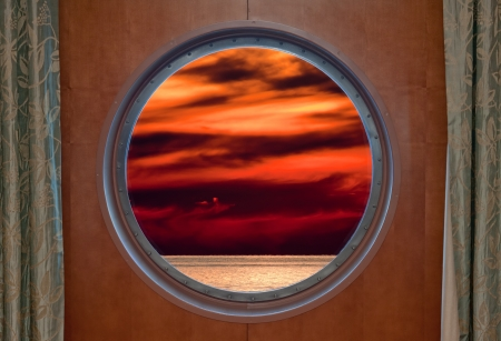 sunsets: View of a sunset through a cruise ship porthole. Stock Photo
