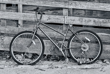 parked: An abandoned bike leaning against a wooden fence.