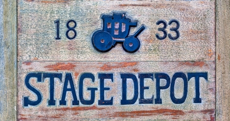 A stage depot sign made from wood. There is a picture of a stagecoach on it.