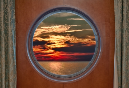 ship porthole: Dramatic Sunset Seen Through a Ship Porthole. Several colors including fiery red are seen in the sky above the ocean.