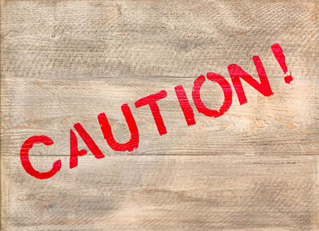 The word Caution written in red across a wooden crate 版權商用圖片