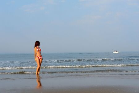 Beautiful girl looking at the boat on the ocean beach photo