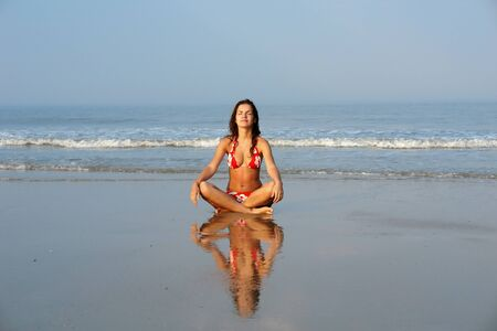 Beautiful girl doing yoga on the ocean beach photo