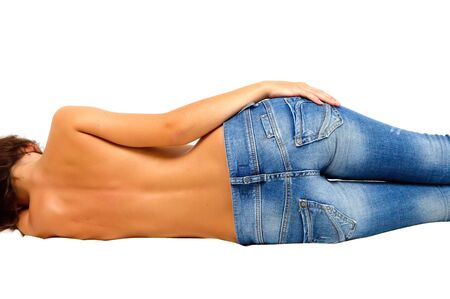 Topless girl in blue jeans laying on floor photo
