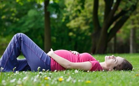 Mujer embarazada joven que se relaja en el parque