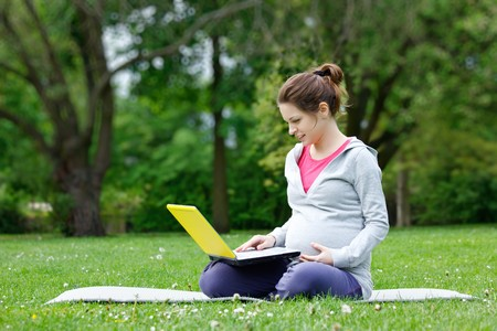 Young pregnant woman with laptop in the park photo