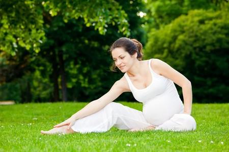 vientre femenino: Joven mujer embarazada ejercer en el Parque