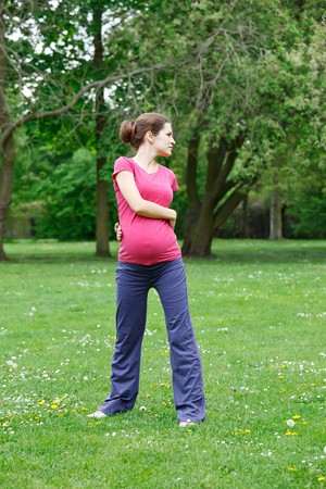 Beautiful pregnant woman exercising in the park photo