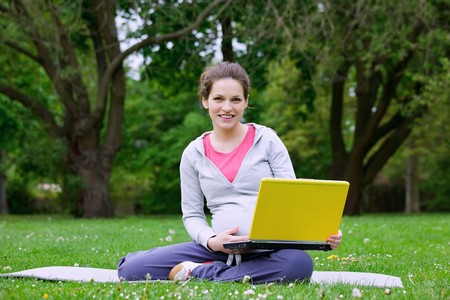 Beautiful pregnant woman with laptop in the park Stock Photo - 7246790
