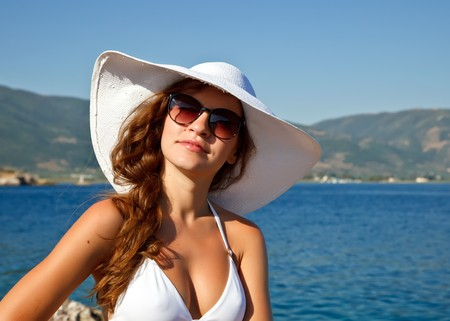 Outdoor portrait of young woman in white hat photo