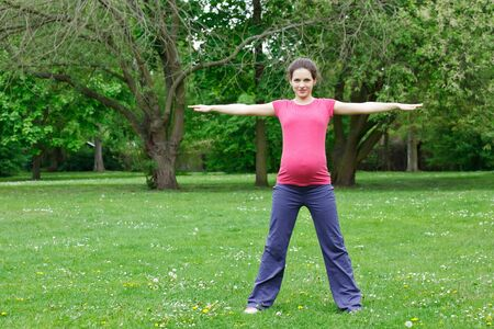 Pregnant woman exercising in the park photo
