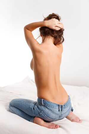 Back of a topless girl in blue jeans Stock Photo - 7893628