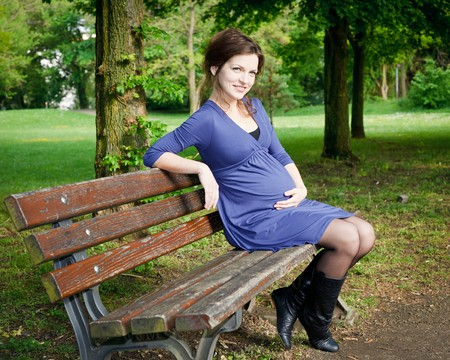mother on bench: Beautiful pregnant woman sitting on bench