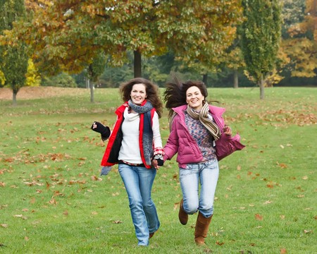 Two pretty girls having fun in autumn park Stock Photo - 8160572