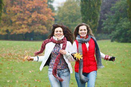 Two pretty girls having fun in autumn park Stock Photo - 8160563