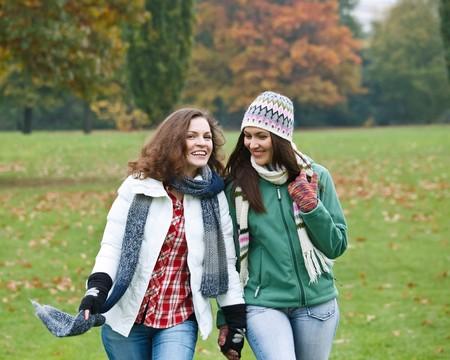 Two pretty girls having fun in autumn park Stock Photo - 8160567