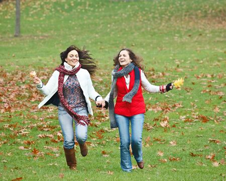 Two pretty girls having fun in autumn park Stock Photo - 8234116