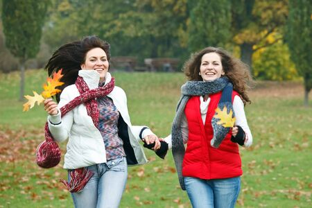 Two pretty girls having fun in autumn park photo