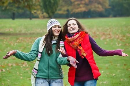 Two pretty girls having fun in autumn park Stock Photo - 8239831