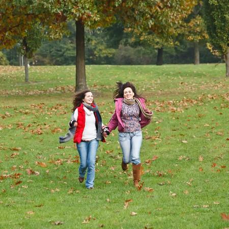 Two pretty girls having fun in autumn park photo