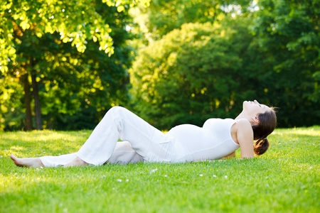 Beautiful pregnant woman relaxing in the park photo