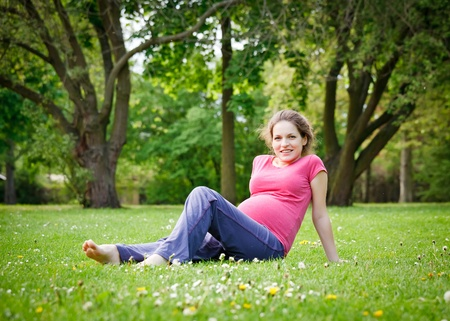 Beautiful pregnant woman in the park photo