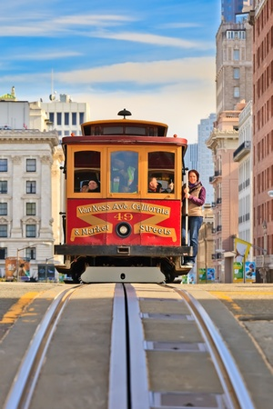 trolley: SAN FRANCISCO - NOVEMBER 26, 2010: Passengers enjoy a ride in a cable car in San Francisco, California. It is the oldest mechanical public transport in San Francisco which is in service since 1873.