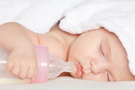 Sleeping baby with bottle photo