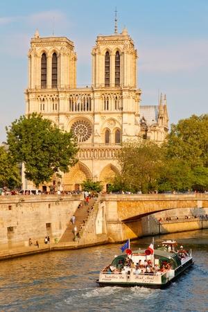 PARIS - APRIL 24: Tourists enjoy a boat trip on Seine river near Notre Dame cathedral on April 24, 2011 in Paris. Notre Dame de Paris receive 12 million visitors annually.