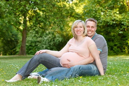 Pregnant couple resting in the park photo