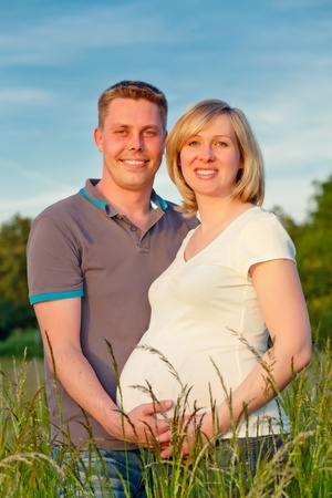 Pregnant couple in the park photo