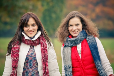 naturally: Two young woman walking in autumn park