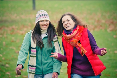 two women talking: Two young woman walking in autumn park