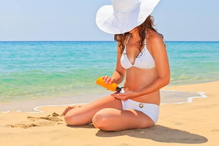 sun protection: Young woman enjoy sun on the beach Stock Photo