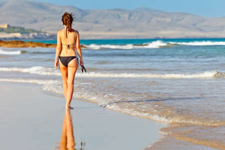 Young woman walking on the beach photo