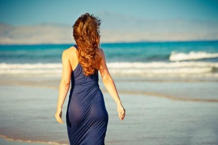 hintern: Junge Frau posiert am Strand