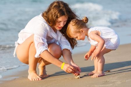 klein meisje op strand: Moeder met kleine dochter op het strand