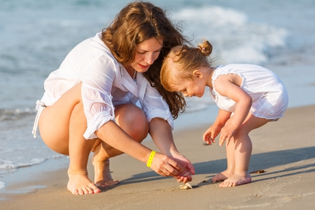 babies playing: Mother with little daughter on the beach