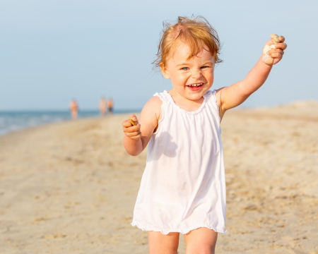Little girl running on the beach photo