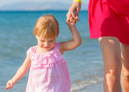 Little girl walking on the beach photo