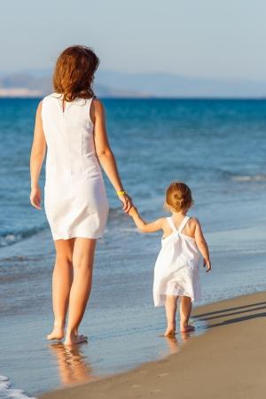 ni�os caminando: Madre e hija en la playa Foto de archivo