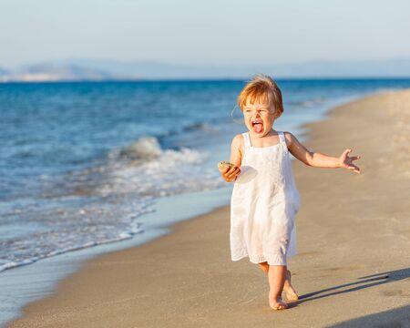 Little girl running on the beach photo