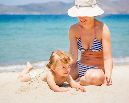 Mother with little daughter on the beach photo