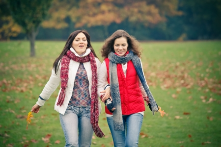 Two young woman walking in autumn park photo