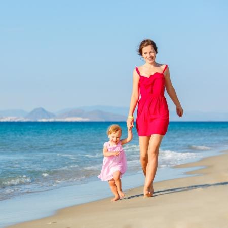 niños caminando: Madre e hija en la playa Foto de archivo
