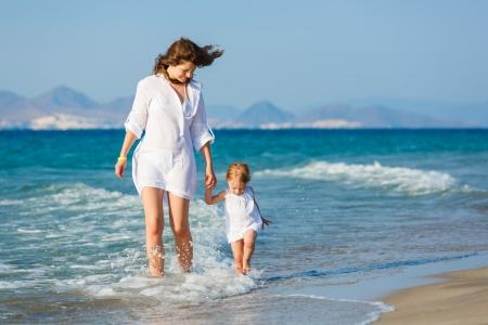 Mère et petite fille marche sur la plage