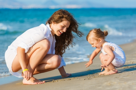 kids playing water: Mother playing with little daughter on the beach