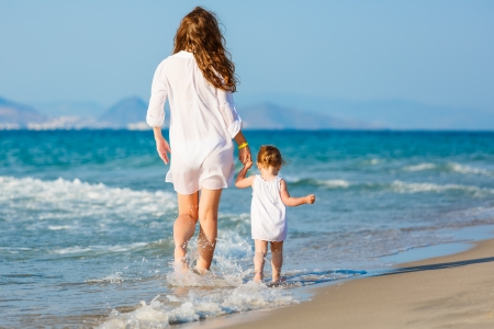 Mother and little daughter walking on the beach photo