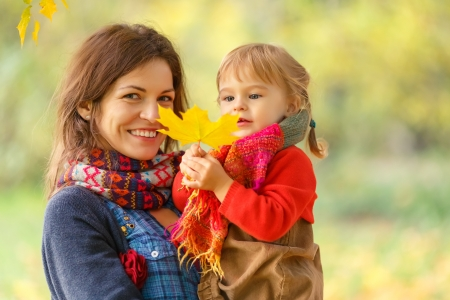 vibrant colors: Little girl and her mother in the autumn park Stock Photo